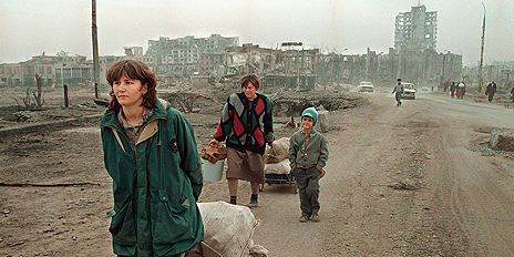 Civilians move through the devastated city of Grozny