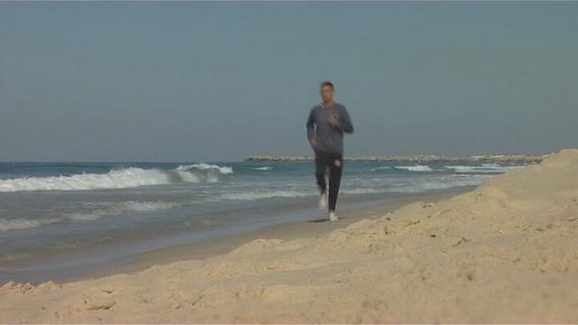 Nader el Masri running along the beach in Gaza