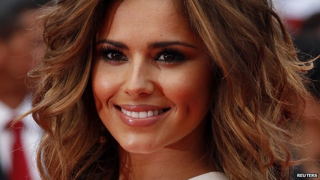 Cheryl Cole appears at a recent film premiere. She has a beaming smile. Her hair is now light brown and lightly curled.