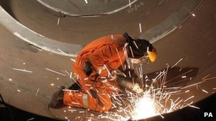 Worker using a grinder