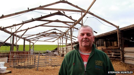 Farmer Alan Barrow stood beside a barn that blew over in high winds