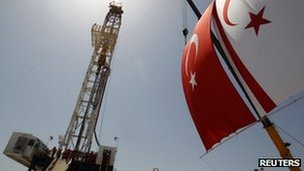 Turkish and Turkish Cypriot flags wave next to a drilling tower at Trikomo northern Cyprus