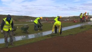 Workmen laying grass on Giant's Causeway centre roof