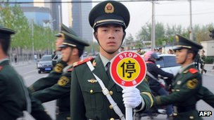 Chinese embassy guards march towards the US embassy compound in Beijing on April 27, 2012, amid unconfirmed reports that blind lawyer Chen Guangcheng was currently at the US embassy.
