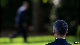 Secret Service agent watches as President Barack Obama walks in the White House grounds, 27 April 2012