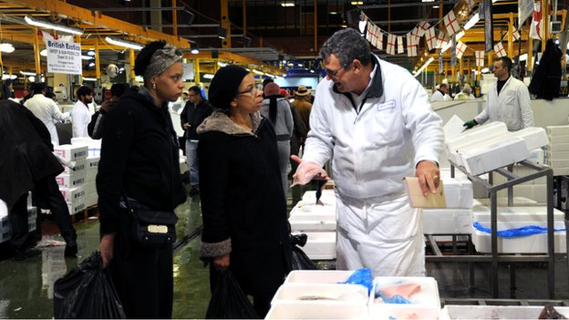 A woman choosing fish to buy at Billingsgate Market