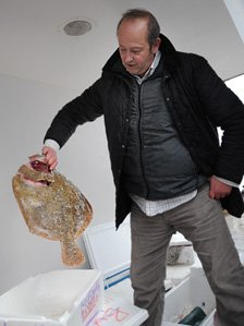 Rex Goldsmith holds up a fish in the back of his delivery van