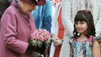 Queen Elizabeth II holds flowers given to her by a local girl (name not given) during a walkabout in the centre of Windsor
