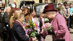 Queen Elizabeth II is given flowers by local school children during a walkabout in the centre of Windsor, after departing from Windsor Castle with the Duke of Edinburgh