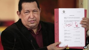 Venezuela President Hugo Chavez holds up copy  of new labour law on 30 April 2012