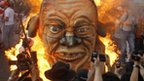 Protesters burn an effigy of President Benigno Aquino during a rally in Manila on May 1, 2012