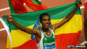 Kenenisa Bekele of Ethiopia holds his country's flag after winning the gold medal in the Men's 5,000m at China's National Stadium in Beijing, 23 August 2008