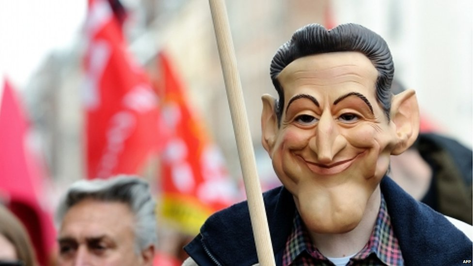 A demonstrator wearing a mask Nicolas Sarkozy, 1 May 2012.