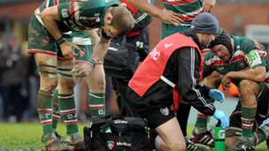 A member of Leicester Tigers coaching staff attends to an injured player