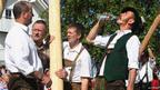 Men gathered around a wooden pole, one drinking water, 1 May 2012.