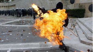 Person dressed in black throwing a petrol bomb
