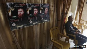 Bassam Diab sits next to posters depicting his brother, Bilal, at his home  near the West Bank town of Jenin