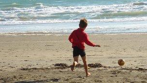 Boy playing football on beach