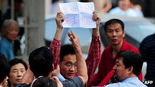 A protester with a banner supporting blind rights activist Chen