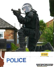 Police officer with baton round gun
