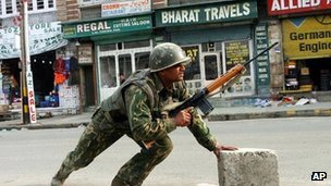 An Indian paramilitary soldier takes cover during a gun battle with militants in Srinagar, India.