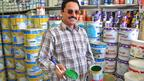 A man stands in front of pots of paint