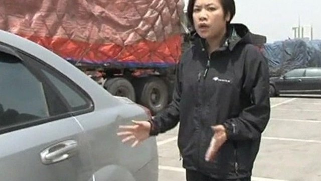 Reporter from Hong Kong Cable TV shows damage on a car