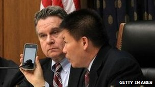 US Rep Chris Smith (2nd L), Rep Frank Wolf (L) and president of ChinaAid Bob Fu (R) listen to Chen Guangcheng on the phone during a hearing of the Congressional-Executive Commission on China on 3 May 2012 in Washington, DC