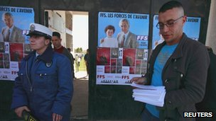 A supporter of the Socialist Forces Front (FFS) party (R) hands out leaflets before their parliamentary election campaign rally in Tizi Ouzou, Algeria 