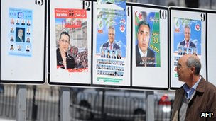 A man walks past candidates' election posters in Algiers