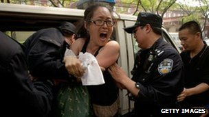 A protester is removed by police from outside the Beijing hospital where activist Chen Guangcheng is staying, 4 May