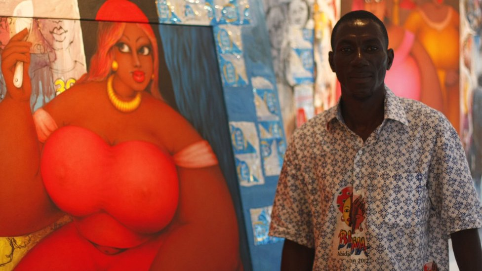 Artist Augustin Kassi in front of one of his large lady paintings - Abidjan, Ivory Coast, 3 May 2012