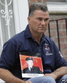 Retired firefighter Jim Riches poses for a picture with a photography of his son near his home in New York May 3, 2012