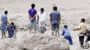 Police and military personnel, aided by civilian volunteers, dig through mud and silt during rescue operations 