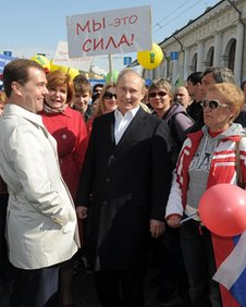 Vladimir Putin, centre, with Dmitry Medvedev and supporters at the May Day parade in Moscow