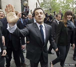 Nicolas Sarkozy, accompanied by his wife Carla Bruni, waves after voting in Paris, 6 May