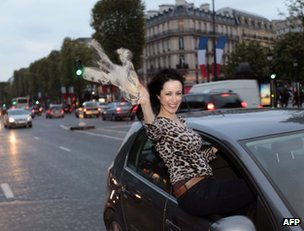 A Hollande supporter cheers from a car in Paris, 6 May