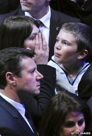Carla Bruni shields her face during the speech by her husband, Nicolas Sarkozy, in Paris, 6 May