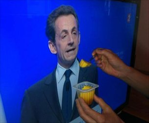 An image showing someone offering pudding to an image of Nicolas Sarkozy, 6 May 