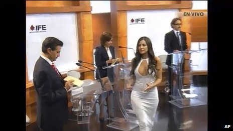 In this screen grab taken from Mexico's Federal Electoral Institute's YouTube channel, Julia Orayen, second from right, carries a box to presidential candidates