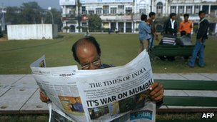 An Indian man reads a newspaper in Delhi on 27 November 2008