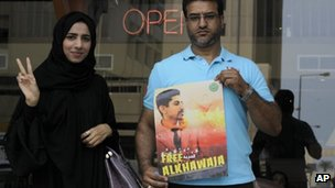 Two Bahrainis hold up a poster demanding the release of Abdulhadi al-Khawaja outside a court in Manama (8 May 2012)