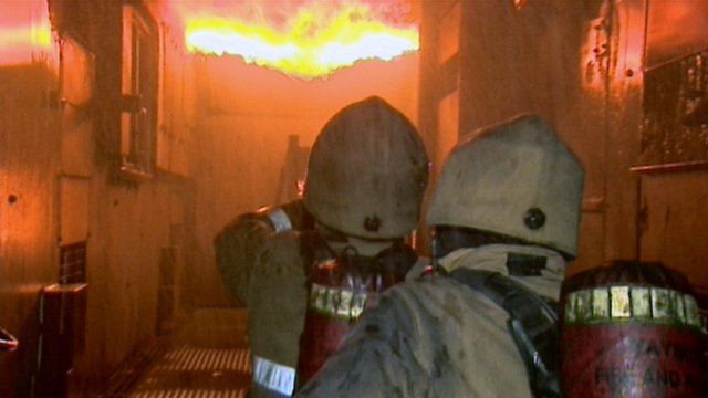 Firefighters tackle a burning building during a training exercise