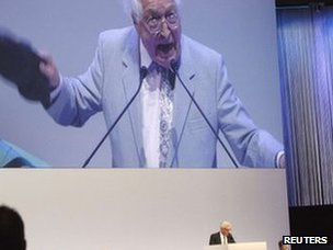 An unidentified shareholder is seen on a huge screen as he holds up his shoe while Swiss bank Credit Suisse