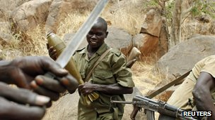 A SPLA-N fighter stands with a mortar shell near Jebel Kwo village in the rebel-held territory of the Nuba Mountains in South Kordofan, 2 May 2012