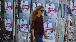 Woman walks past Greek election posters