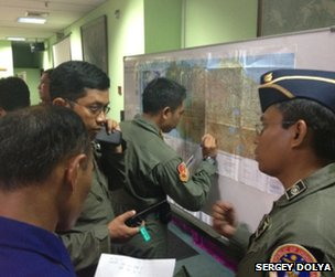 Indonesian officials plot the plane's movements on a map in Jakarta, 9 May (photo: Sergey Dolya)