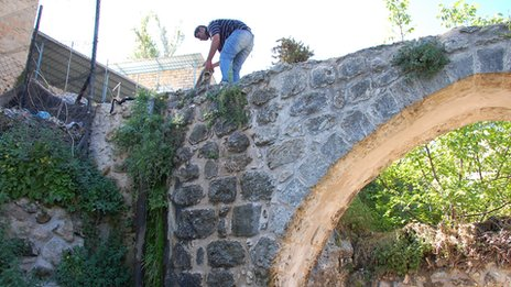 Man changes the water supply channel on a aqueduct in Battir