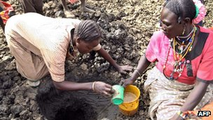 Women fetch murky water on 22 March 2012 from a hole dug near a dried well in Jamam, South Sudan