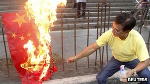 An activist burns a flag of China during a rally in front of the Chinese consular office in Makati&#039;s financial district of Manila on 8 May, 2012